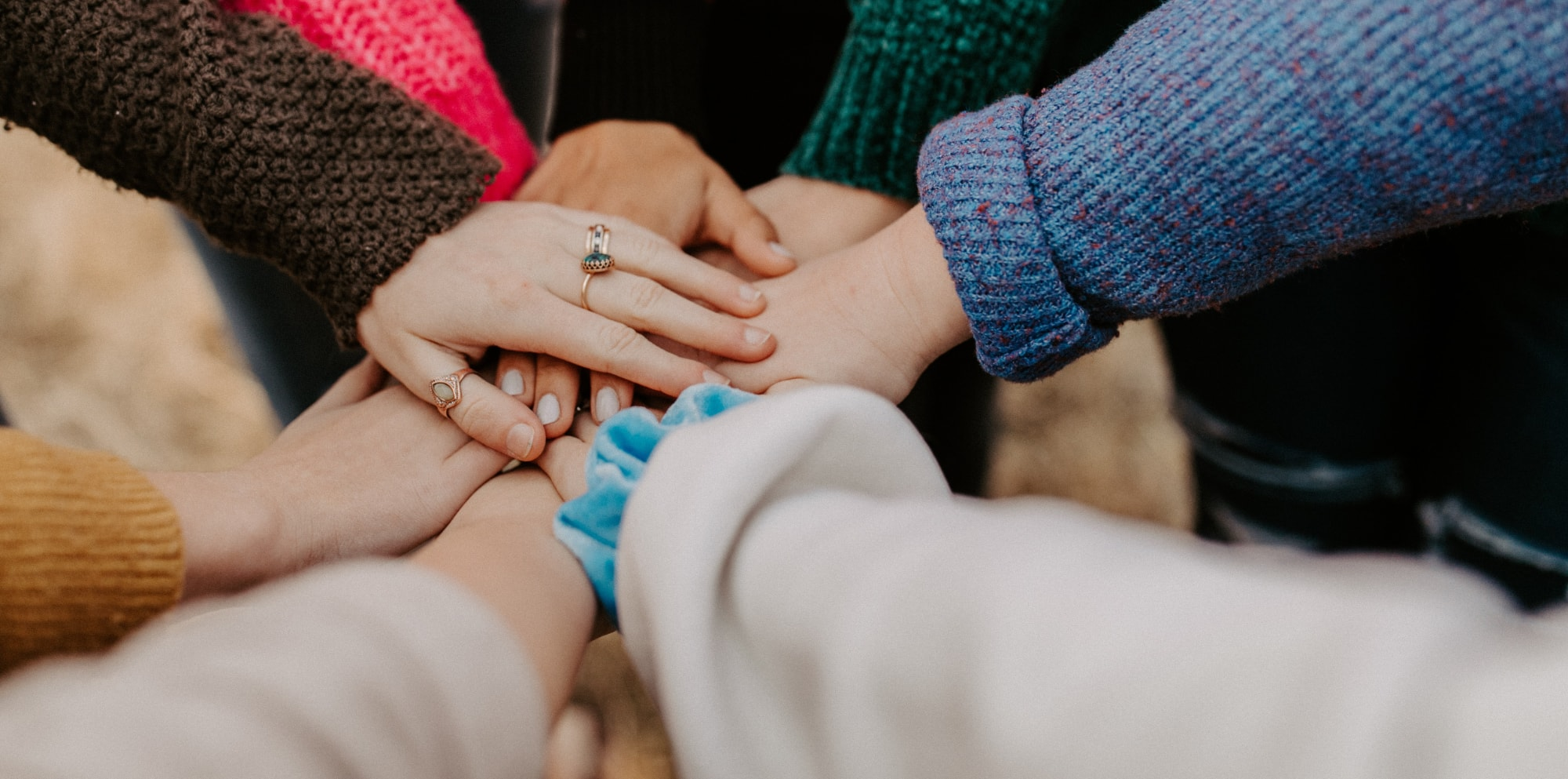 Photo by Hannah Busing, showing hands of a group of people creating common expression of community