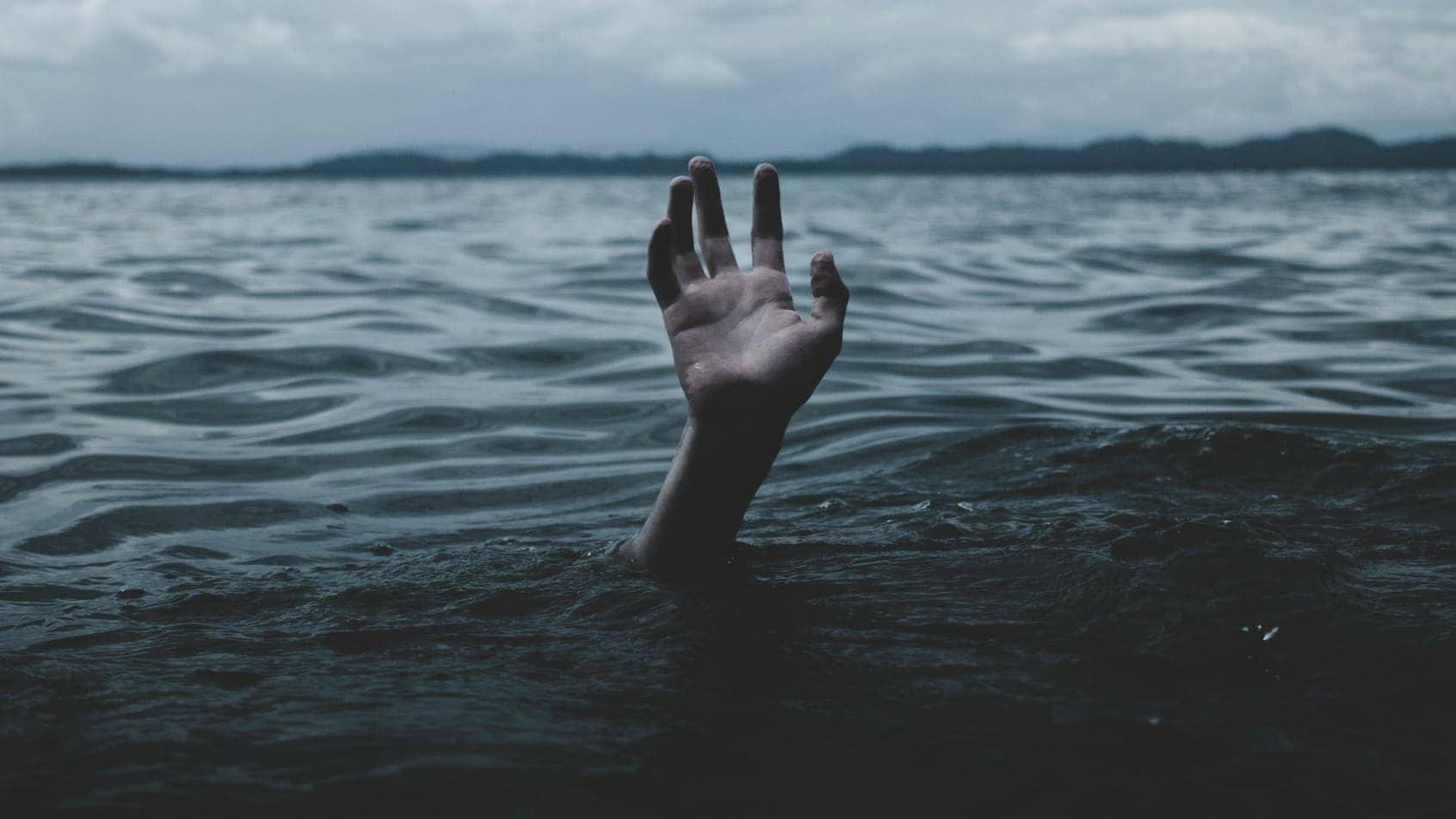 Ertrinken? Hand ragt aus dem Wasser
